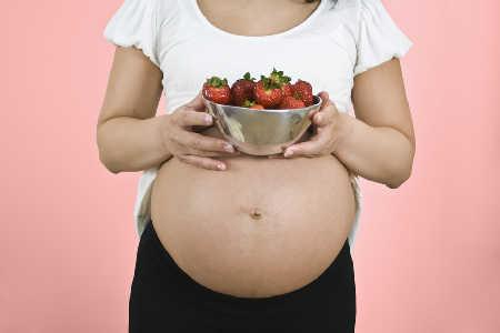 Kobieta w ciąży jedząca truskawki