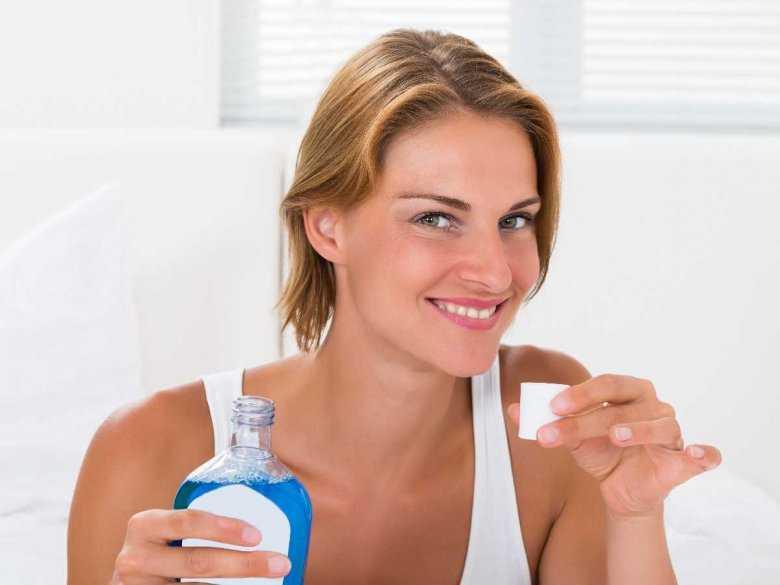 Kobieta używająca płynu do płukania jamy ustnej